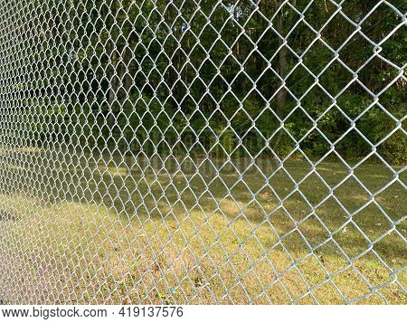 Wide Angle Looking Through Chain Link Fence Bright In Sunlight With Forest Beyond
