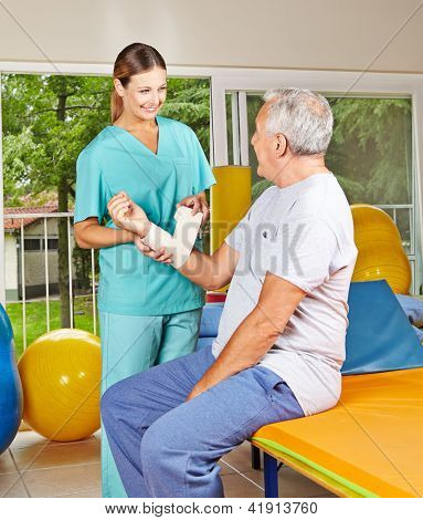 Smiling female hysiotherapist helping senior man in rehab