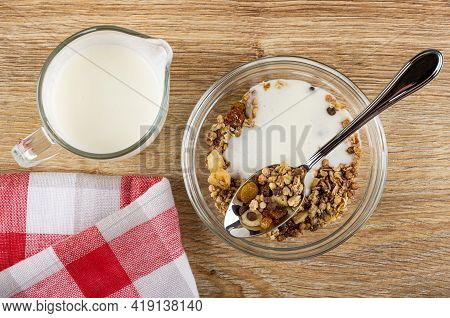 Pitcher With Yogurt, Spoon In Transparent Glass Bowl Of Granola With Banana And Chocolate With Yogur