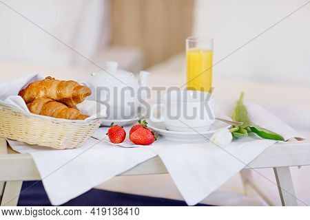 A Wooden Breakfast Table Sits On The Bed In The Hotel. Orange Juice, Strawberries, Croissants Placed
