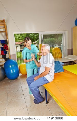 Senior doing remedial gymnastics in physiotherapy with nurse
