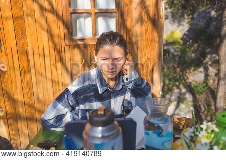 Portrait Of A Young Beautiful Girl Sitting In Front Of A Gadget On The Veranda Of A Summer House On