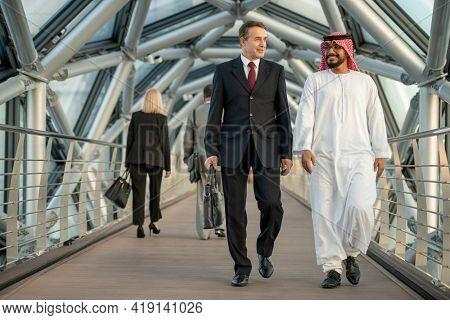 Two intercultural businessmen in formalwear walking inside large modern building and talking