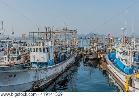 Daecheon, South Korea; April 25, 2021: Fishing Trawlers Moored To Concrete Dock At Seaport Under Ove