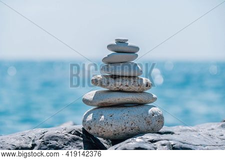 Pyramid Stones On The Seashore On A Sunny Day On The Blue Sea Background. Happy Holidays. Pebble Bea