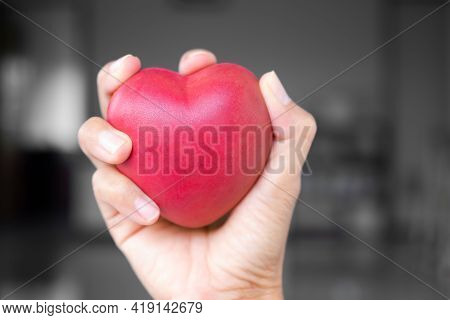 Broken Heart Concept. Close Up Hand Woman Holding And Constrain Red Heart Shape On Blur Black And Wh