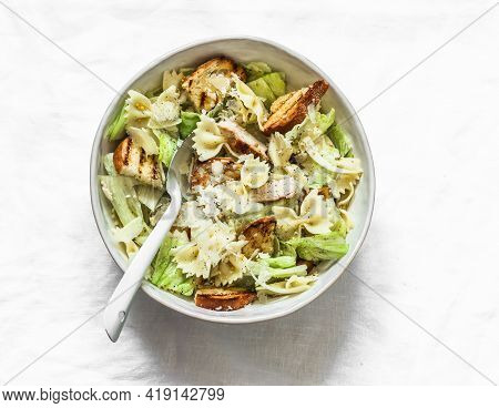 Caesar Pasta Salad In A Bowl On A Light Background, Top View. Delicious Lunch, Snack