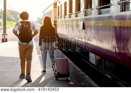 Man & Woman With Backpack Waiting For Train At Railway Station. Loving Couple Traveler Travel Togeth