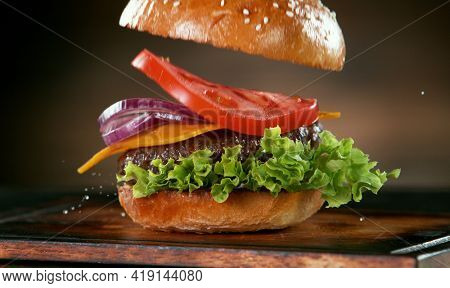 Delicious stacking hamburger on wooden background, flying food concept.