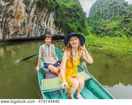 Happy Family Tourists In Boat On The Lake Tam Coc, Ninh Binh, Viet Nam. Its Is Unesco World Heritage