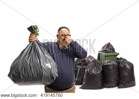 Mature man throwing a smelly waste bag in a bin isolated on white background
