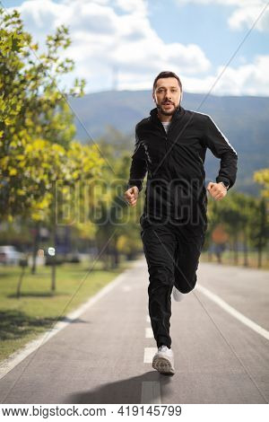 Full length portrait of a young man in black tracksuits running on a jogging lane
