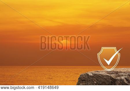 Security Shield With Check Mark Flat Icon On Rock Mountain Over Sunset Sky And Sea, Technology Inter