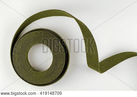 A Roll Of Green Cotton Ribbon On A White Background. Sturdy Tape For Making, Slings, Straps, Sewing