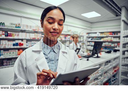 Portrait Of Woman Wearing Labcoat Using Digital Tablet In Drugstore