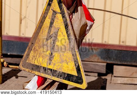 Triangle Shaped Caution Sign About High Voltage Danger. Danger Sign Splashed By Dirt. Warning Symbol