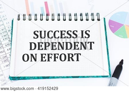 Notebook With Text Success Is Dependent On Effort Lies On The Table With Colored Graphs And Black Ma