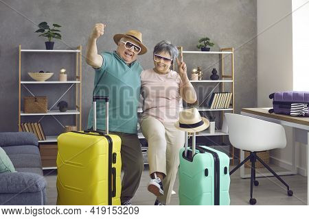 Happy Active Senior Couple Having Fun At Home Before Going On Holiday Trip Together