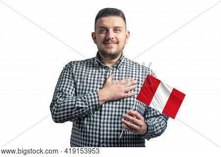 White Guy Holding A Flag Of Peru And Holds His Hand On His Heart Isolated On A White Background With