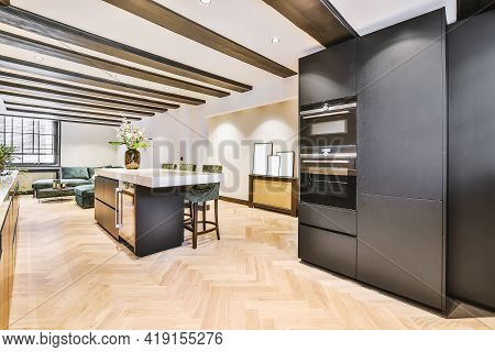 Interior Of Contemporary Open Plan Kitchen With Built In Appliances And Dark Cabinets Under Ceiling