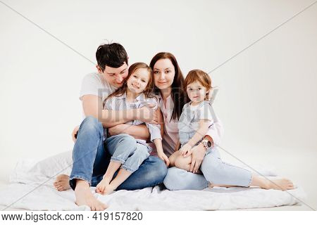 Beautiful Happy Family Cuddling In A White Photo Studio. Backstage.