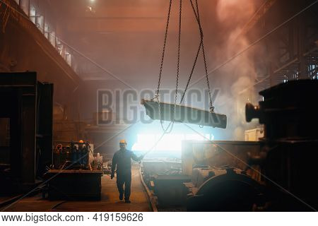 Steel Factory, Metallurgical Plant Interior With Worker Controlling Large Iron Part On Crane, Heavy