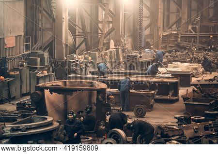 Large Workshop With Metallurgical Plant Workers Working With Cast Iron Parts, Post-casting Processin