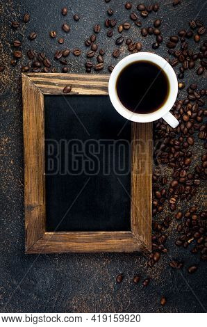 Empty Black Frame With White Cup Of Black Coffee And Coffee Beans On Dark Concrete Background. The C
