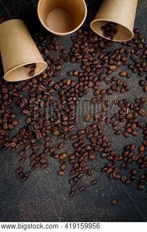 Craft Paper Cups For Coffee And Coffee Beans On Dark Concrete Background. The Concept Of Hot Drinks