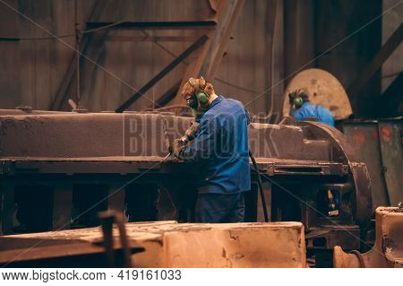 Worker In Workshop Processes Large Cast Iron Part After Casting In Metallurgical Foundry Plant.