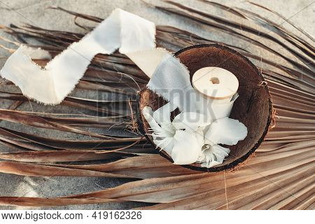 Summer Tropical Lifestyle Scene. Oleander Blossoms And White Silk Ribbons Spools In Coconut Shell. D