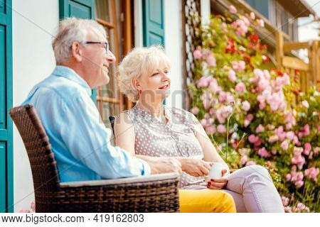 Senior couple enjoying their coffee on porch in front of their house