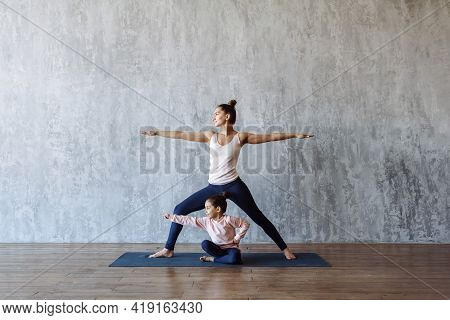 Sporty Happy Family Mom And Daughter Child Doing Yoga Together On The Mat In The Gym Against The Bac