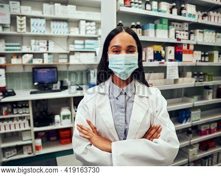 Female Pharmacist Wearing A Coronavirus Covid Mask While Standing In Her Pharmacy