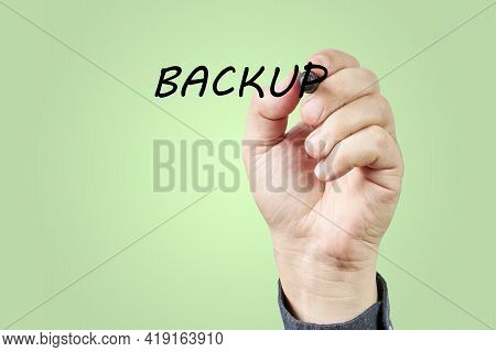 Hand Of Man Writing The Word Backup On A Transparent Board. Backup Concept