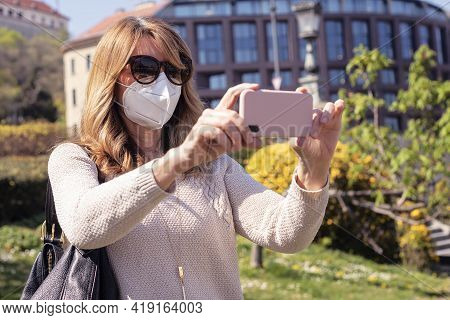 Shot Of Mature Woman Wearing Face Mask While On Sightseeing And Taking Pictures With Her Mobile Phon