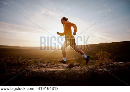 Fit Young Athlete Man Running Up A Hill During Sunrise