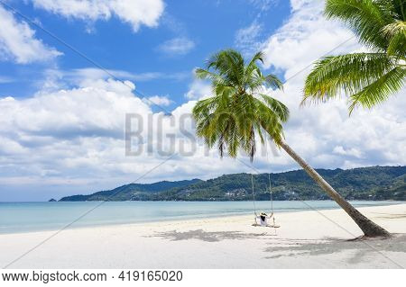 Phukdt, Thailand. Tropical Beach Paradise With Beach Swing With Girl In White Shirt. Women Relax On