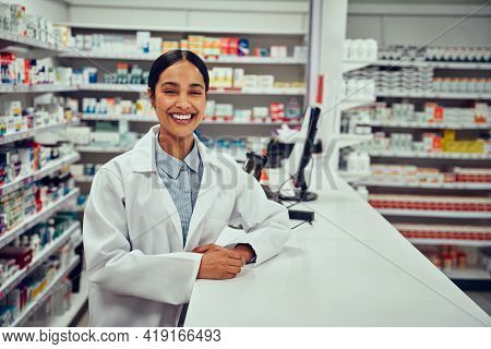 Portrait Of Smiling Happy Confident Young Woman Pharmacist Leaning On A Desk In The Pharmacy