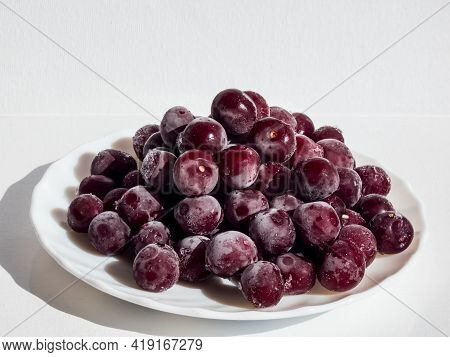 Frozen Sweet, Ripe Cherry Berries Covered With White And Melting Hoarfrost On White Plate With White