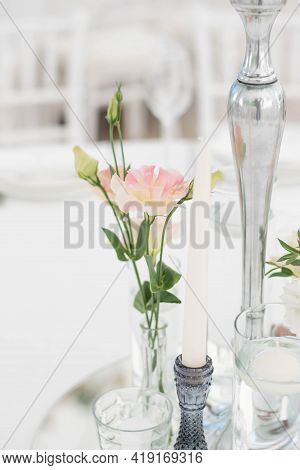 Close-up Of A Wedding Dinner Table At Reception. Fresh Flowers And Candles On Mirros Plate. Wedding