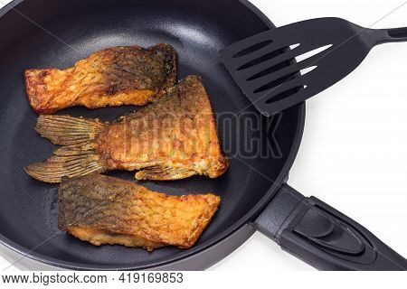Slices Of Fried Carp On Frying Pan With Non-stick Coating And Plastic Spatula On A White Background,