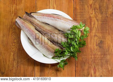 Defrosted Uncooked Carcasses Of The Alaska Pollock Without Of Heads And Tails And Bundle Of Fresh Pa