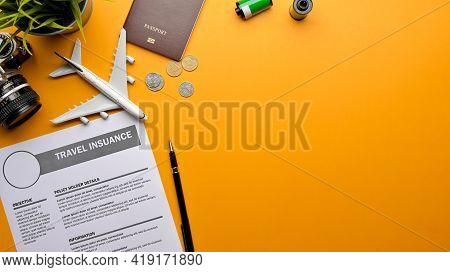 Creative Flat Lay Photo Of Travel Insurance Form, Camera, Passport, Airplane Model And Copy Space On