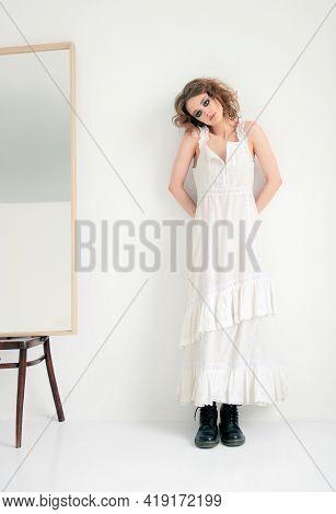 Portrait Of Cute Strange Freaky Girl. Beautiful Sad Woman In White Dress Standing Near The Mirror