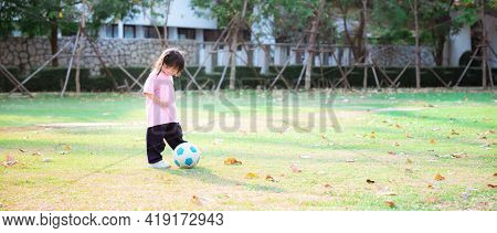 Active Cute Asian Girl Playing Kicking A Blue And White Soccer Ball In The Green Lawn. Exercise On A