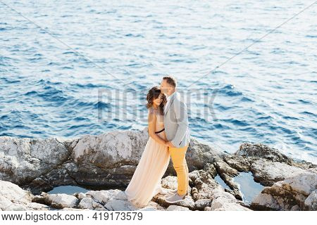 Groom Holds The Brides Hands While Standing On The Rocks Above The Blue Sea. View From Above
