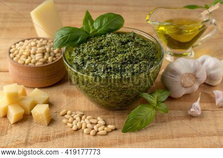 Composition With Bowl Of Yummy Green Pesto Sauce And Ingredients On Wooden Table. Classic Homemade S