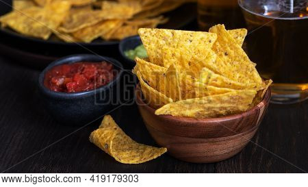Nachos With Guacamole, Red Chilli Sauce And Beer  On Wooden Table The Most Famous Mexican Snack Back