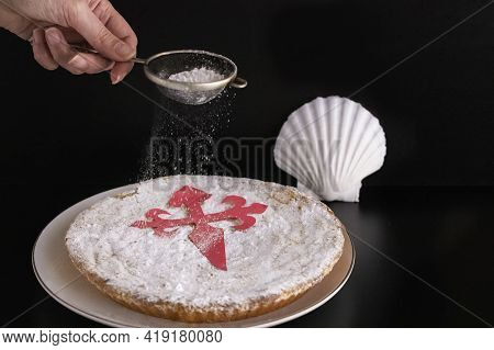 Woman Pouring Sugar For Decorated Tarta De  Santiago Or St. James Cake, Famous Spanish Almond Cake